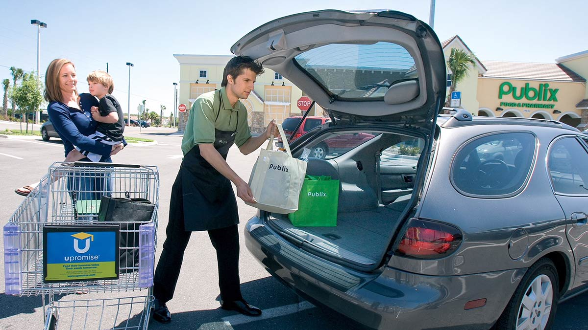 A publix bagger helps a mom load her groceries into her car